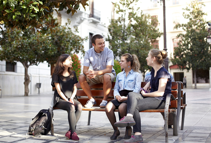 Students sit on a bench in Grenada, Spain