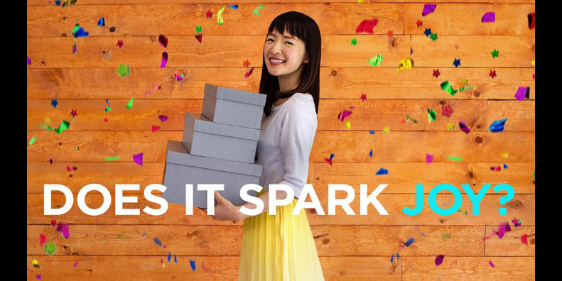 Marie Kondo with boxes and the words Does It Spark Joy?