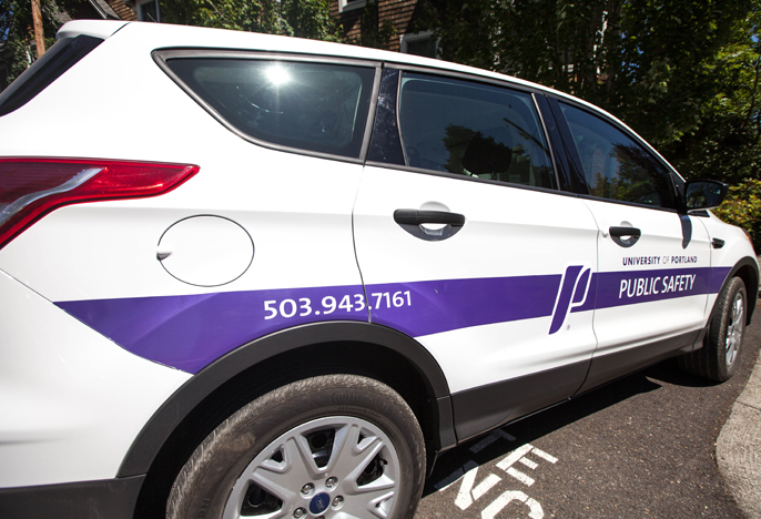 side of a campus safety car. Large white SUV with large purple stripe on the side.