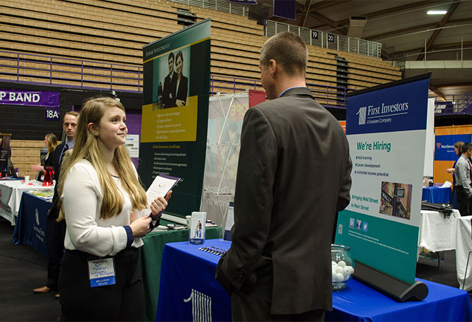 job fair: student holding a resume speaking with an employer in front of a row of tables with posters and information about jobs