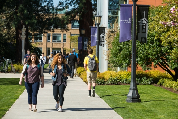 Two female students walking on a campus path
