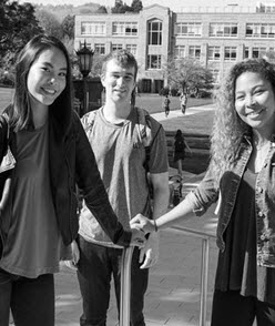 Three students standing on balcony  with campus quad and buildings behind them